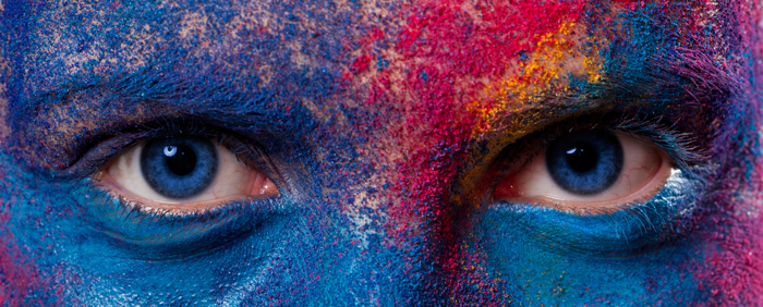 photo of a closeup of person's eyes and forehead covered in many different color paints