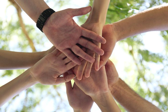 several hands placed upon each other symbolize the camaraderie of our alumni programs