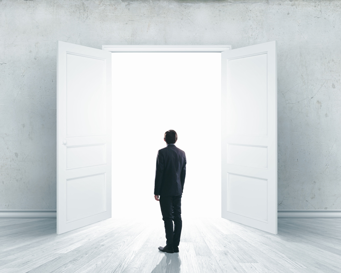 man in front of open door symbolizes taking the next step as many do in our alumni programs
